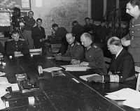 Colonel General Alfred Jodl, previously authorised to do so by Karl Dönitz, signed the unconditional surrender of the Wehrmacht to the Western Allies in Reims on 7 May 1945, which came into force on 8 May.
